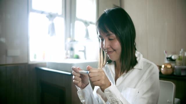 happy woman is pregnant using pregnancy test - ovulazione video stock e b–roll