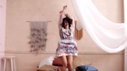 Happy woman jumping on her bed in a cute floral dress. Room with a white curtain. Front footage