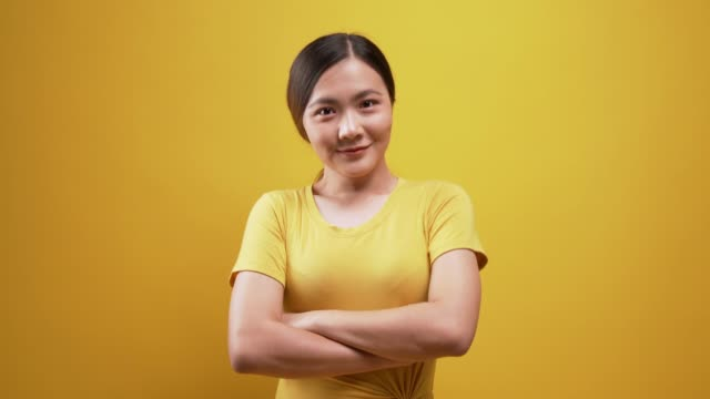 happy woman looking at the camera over isolated yellow background - yellow background stock videos & royalty-free footage