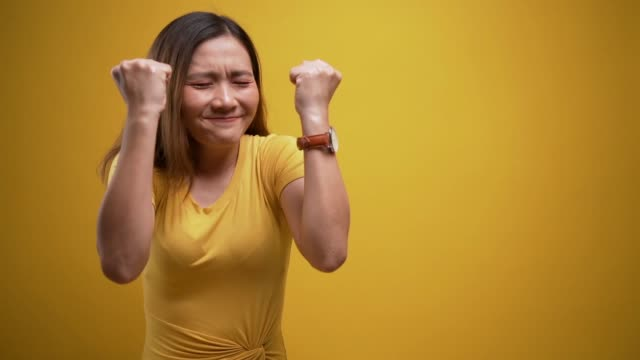 happy woman make winning gesture over isolated yellow background - coloured background stock videos & royalty-free footage