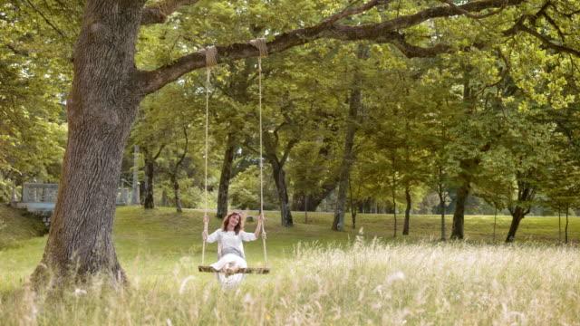SLO MO Happy woman on a swing