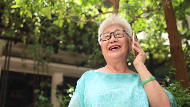 vídeos de stock, filmes e b-roll de mulher feliz em seu telefone - asiático