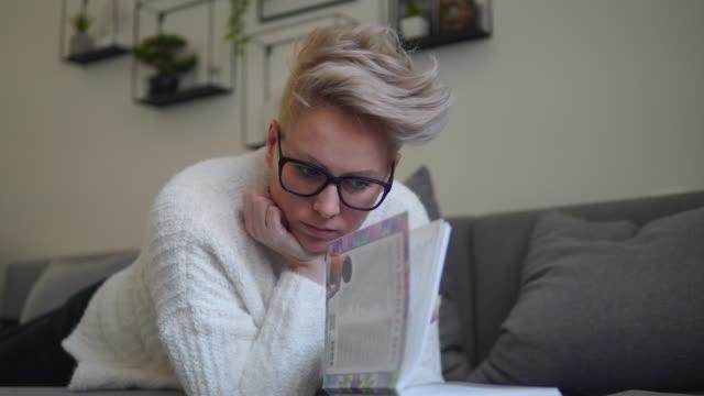 glückliche frau lesen buch auf einer couch zu hause - literatur stock-videos und b-roll-filmmaterial