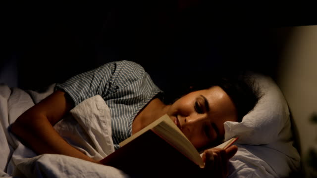 happy woman reading book while lying by man on bed - ora di andare a letto video stock e b–roll