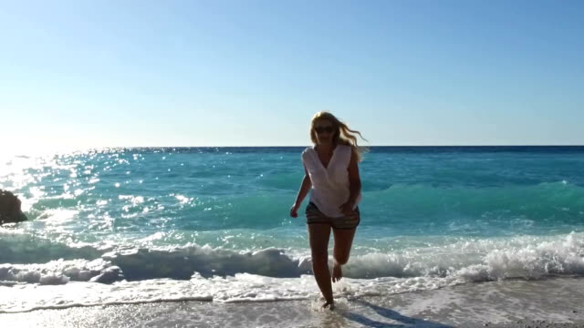 Lycklig kvinna körs på en solbelyst strand