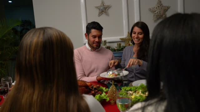 happy woman serving salad to partner all sitting enjoying a christmas dinner - serving size stock videos & royalty-free footage