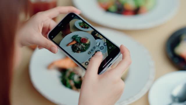幸せな女性は、ソーシャルネットワークのための健康的な食べ物の写真を共有します。 - ブログ点の映像素材/bロール