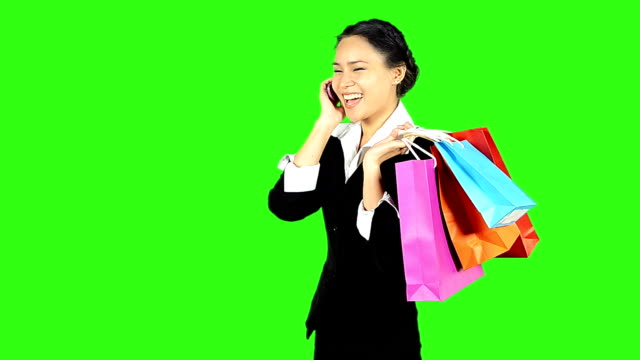 stockvideo's en b-roll-footage met happy woman shopping and talking telephone on green screen background - keyable