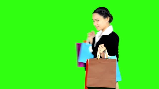 vídeos de stock e filmes b-roll de mulher feliz compras sobre fundo verde de ecrã - codificável