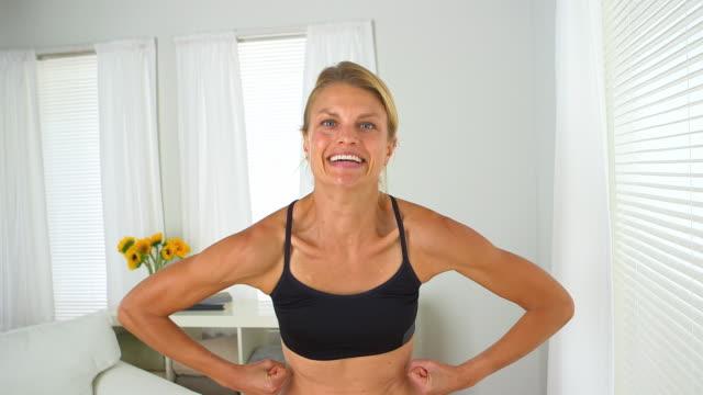 happy woman showing off her muscles - 30代の女性一人点の映像素材/bロール