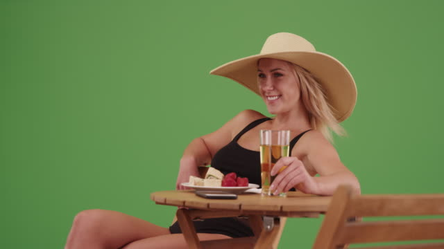 happy woman sitting in her swimsuit with a beer on green screen - zurücklehnen stock-videos und b-roll-filmmaterial