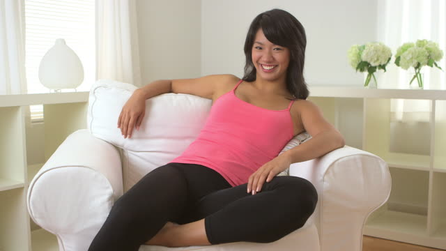 Happy woman sitting in sofa chair in living room