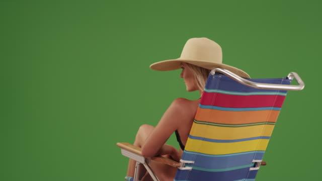 vídeos de stock e filmes b-roll de happy woman sitting on a lounge chair on green screen - sunbathing