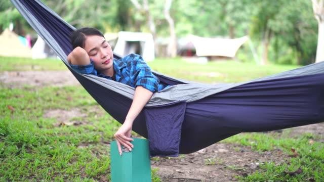 stockvideo's en b-roll-footage met happy woman sleeping in swinging hammock at campground - een dutje doen