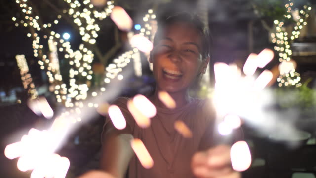 happy woman smiling with sparklers - carefree stock videos and b-roll footage