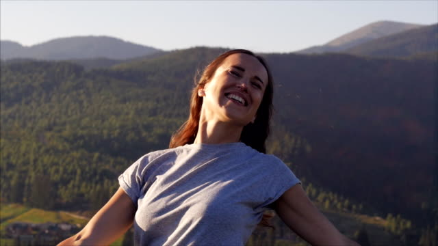 happy woman spinning at sunset in mountains - arms outstretched stock videos & royalty-free footage