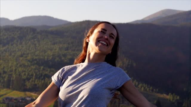 stockvideo's en b-roll-footage met gelukkige vrouw spinnen bij zonsondergang in bergen - positieve emotie