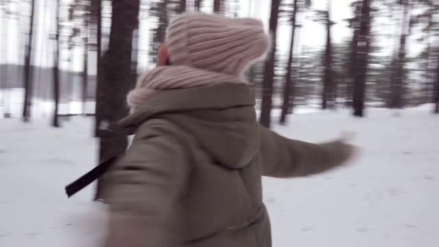 happy woman spinning under snowfall with stretched arms in the snowy forest - mitten stock videos and b-roll footage
