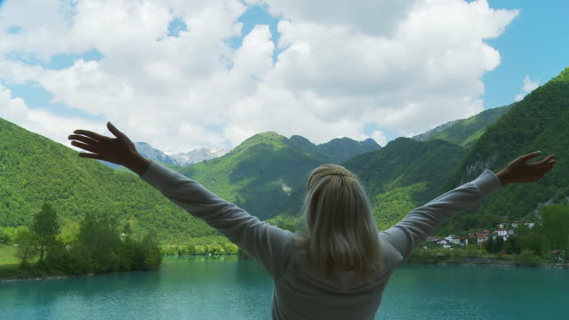 stockvideo's en b-roll-footage met hd: happy woman stretching arms at the lake - julian alps