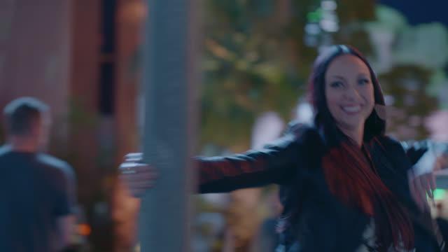 vidéos et rushes de happy woman swings around light pole on las vegas street corner at night. - quadragénaire