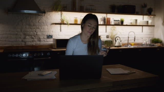 happy woman taking a break from working at home with laptop buying something online using her smartphone and credit card - multitasking woman stock videos & royalty-free footage
