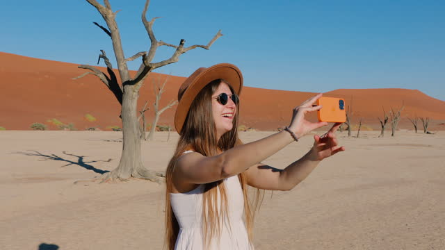 happy woman taking selfie by phone at the deadvlei  in namib desert, namibia - white dress stock videos & royalty-free footage