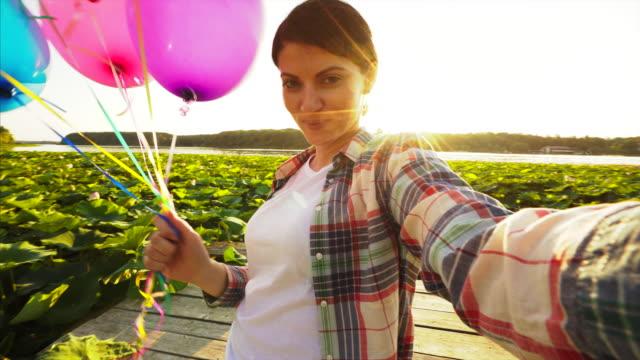 Happy woman taking selfie on the pier.