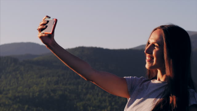 Happy woman taking selfie with phone in the mountains
