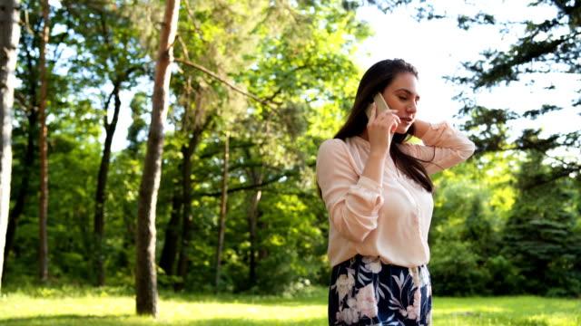 vídeos y material grabado en eventos de stock de mujer feliz hablando por el teléfono móvil - mujeres jóvenes