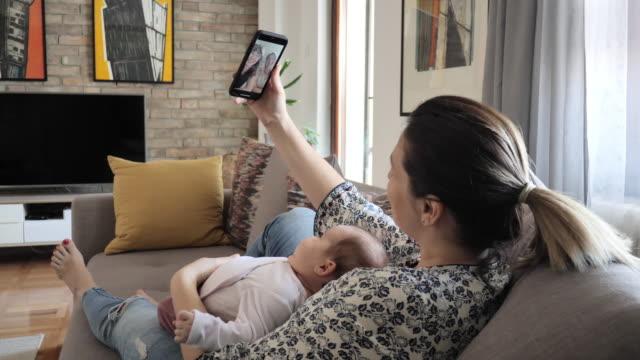 vídeos de stock, filmes e b-roll de mulher feliz conversando com a família por chamada de vídeo no celular - sentir a falta emoção