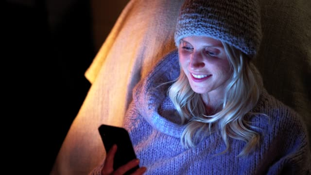 stockvideo's en b-roll-footage met happy woman sms'en op de telefoon op camping night - muts