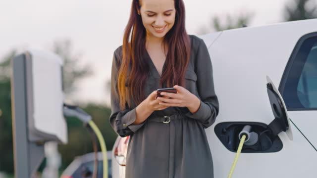 vídeos y material grabado en eventos de stock de slo mo mujer feliz usando su teléfono inteligente mientras espera a que su coche sea cargado - coche híbrido