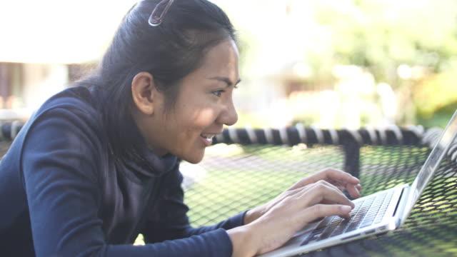 glückliche frau mit laptop im resort am wochenende - freibad stock-videos und b-roll-filmmaterial