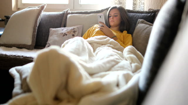 happy woman using mobile phone on sofa in the morning - reclining stock videos & royalty-free footage