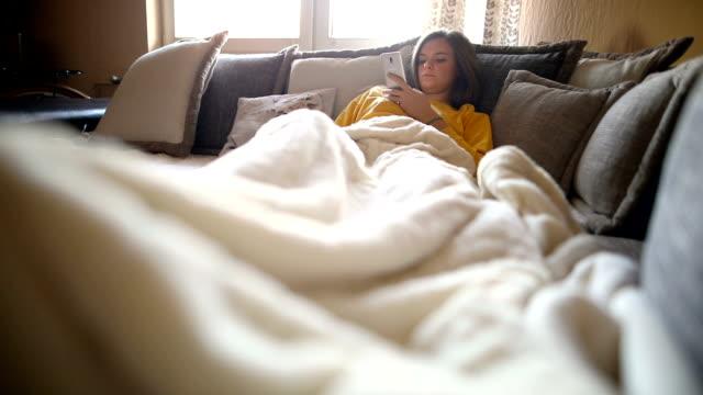 vídeos de stock e filmes b-roll de happy woman using mobile phone on sofa in the morning - almofada roupa de cama