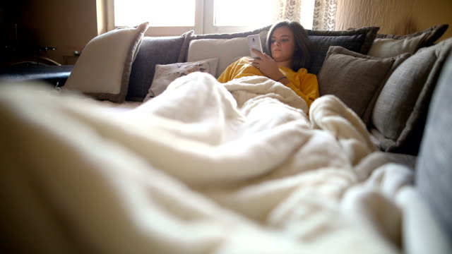 happy woman using mobile phone on sofa in the morning - lying down stock videos & royalty-free footage