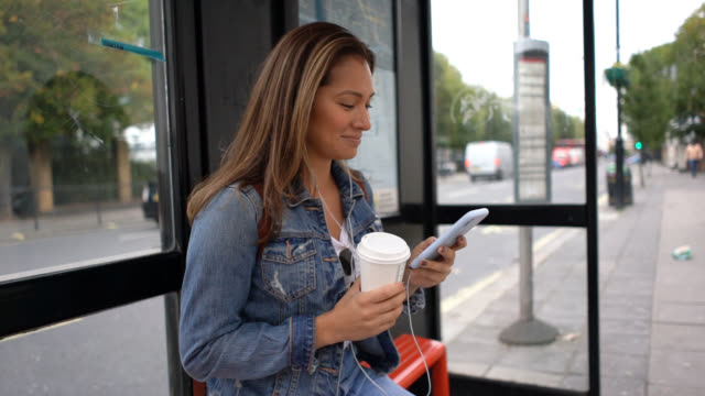 happy woman waiting for the bus and looking at her cell phone while drinking coffee and listening music - cuffia attrezzatura per l'informazione video stock e b–roll