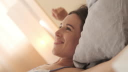 Happy woman waking up and stretching in bed