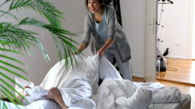 Happy woman waking up man and playing pillow fight