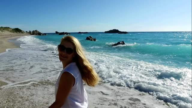 Gelukkige vrouw lopen op een zonovergoten strand
