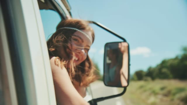 happy woman waving hands through van window - furgone video stock e b–roll