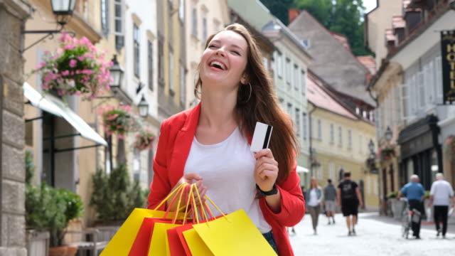 vidéos et rushes de femme heureuse avec des sacs à provisions et la carte de crédit dans le centre d'une ville. - shopaholic