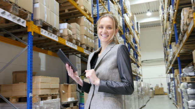 Happy woman with tablet in warehouse