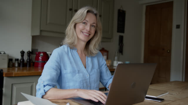 happy woman working at home using laptop while looking at the camera smiling - e commerce stock videos & royalty-free footage
