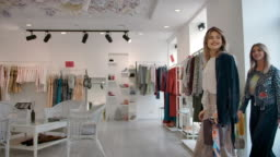 Happy women coming in fashion store