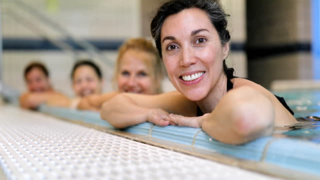 Happy women leaning on poolside at health club