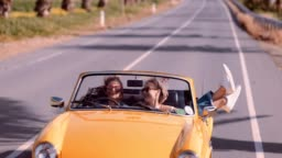 Happy women on road trip driving vintage yellow cabriolet car