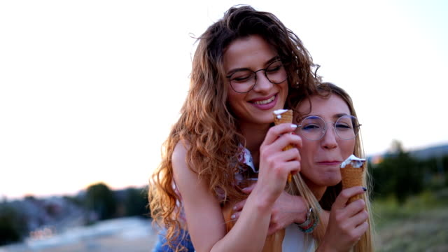 happy women playing piggyback at dusk - piggyback stock videos & royalty-free footage