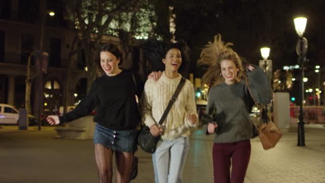 vídeos de stock e filmes b-roll de happy women running on sidewalk at nightlife - vida noturna