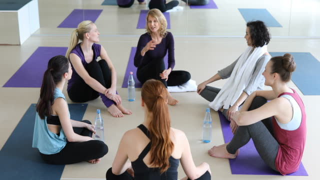Happy women talking while sitting at yoga class